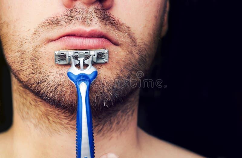 Primer de una maquinilla de afeitar en su barbilla cerdosa imagen de archivo