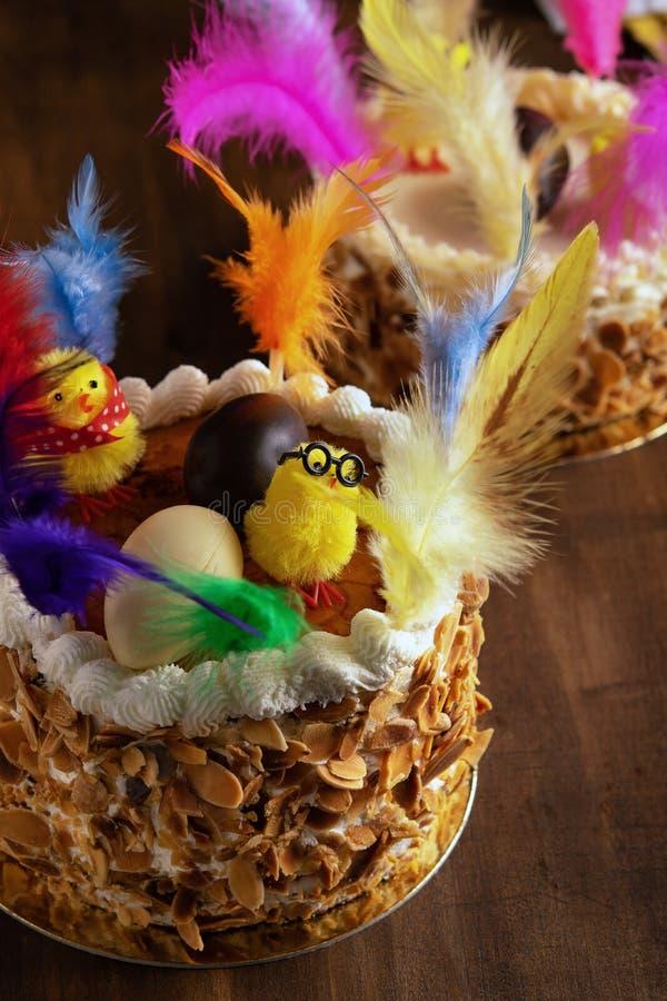 Primer de una Mona de pascua, una torta comida en España en Pascua lunes, adornado con plumas y un polluelo del peluche encendido fotos de archivo