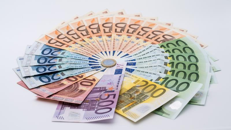 Primer de una moneda un euro con los billetes de banco de diversos valores Cobre el dinero imágenes de archivo libres de regalías