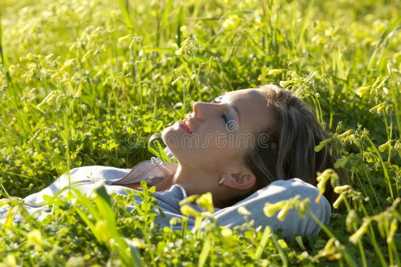 Primer de una muchacha que miente en la hierba verde imagenes de archivo