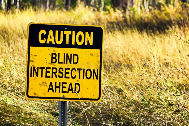 Primer de una muestra ciega de la intersección de la precaución a continuación fotografía de archivo