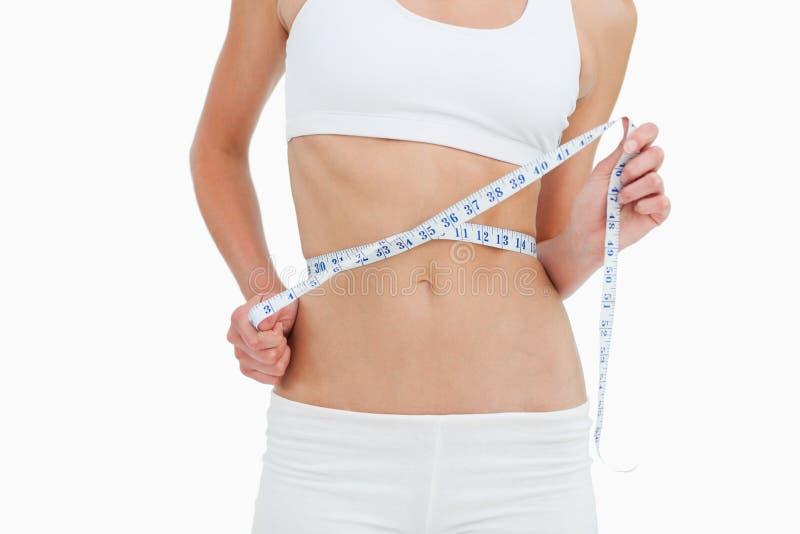 Primer de una mujer en la dieta que mide su cintura fotos de archivo libres de regalías
