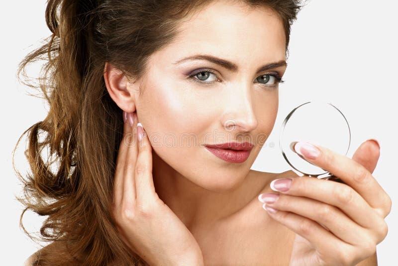 Primer de una mujer hermosa que comprueba su maquillaje en el espejo foto de archivo
