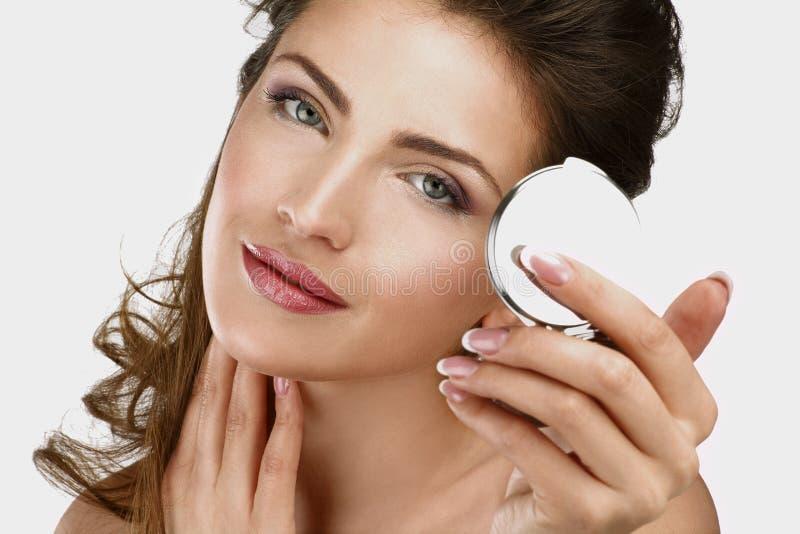 Primer de una mujer hermosa que comprueba su maquillaje en el espejo imagenes de archivo