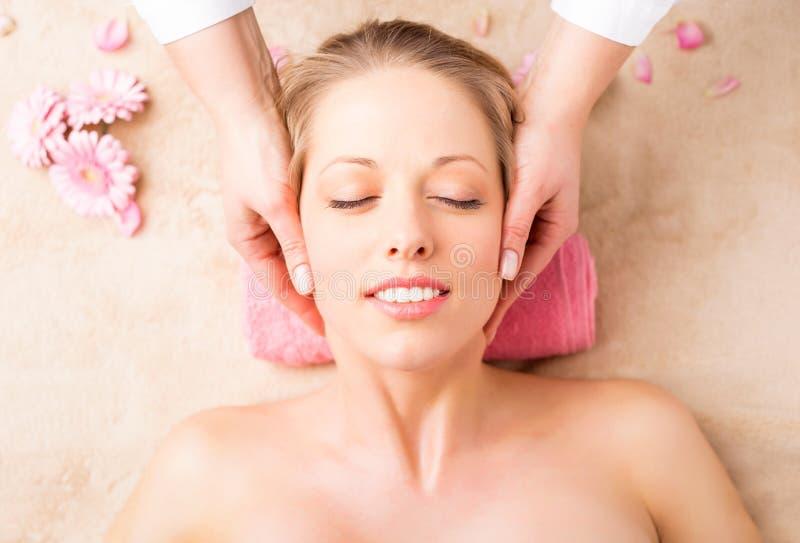 Primer de una mujer joven que consigue masaje de cara fotos de archivo libres de regalías