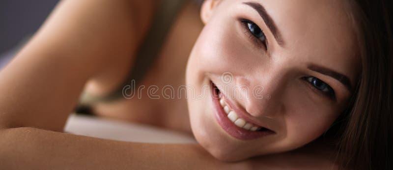 Primer de una mujer joven sonriente que miente en el sofá imagenes de archivo