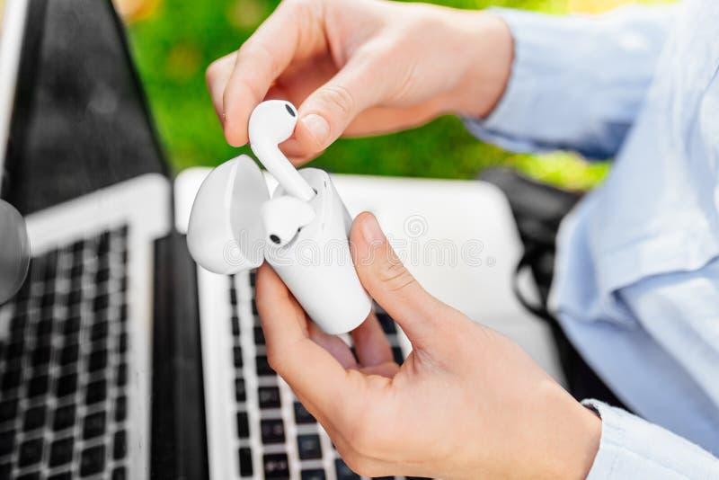 Primer de una mujer sosteniendo los auriculares inalámbricos en una caja blanca en el parque fotografía de archivo