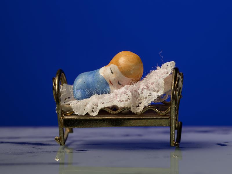 Primer de una pequeña estatuilla de un niño que duerme en cama imágenes de archivo libres de regalías