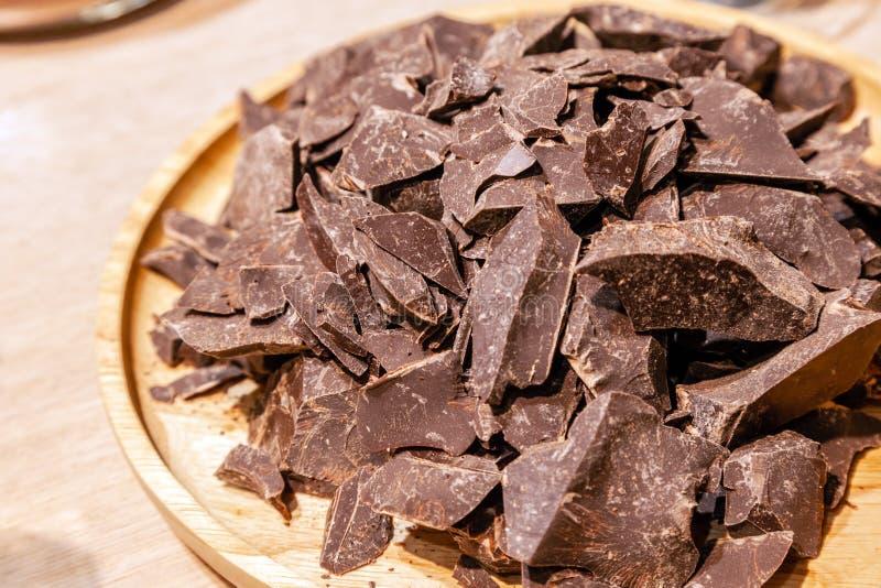 Primer de una pila de pedazos de chocolate oscuro natural en una placa de madera redonda Dieta del concepto, comida sana, postre  imagen de archivo