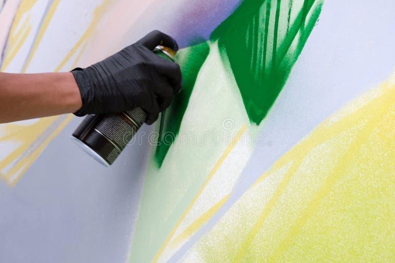 Primer de una pintada de la mano del ` s del artista de la calle Un individuo en un guante negro dibuja una imagen abstracta Vand imagenes de archivo