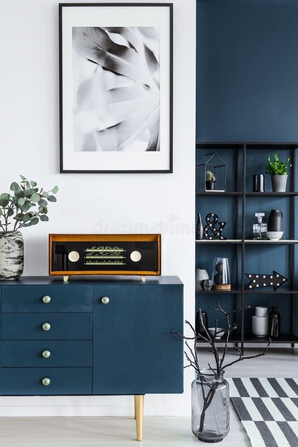 Primer de una pintura, de un gabinete azul, de una radio retra y de un florero del vidrio imagen de archivo libre de regalías