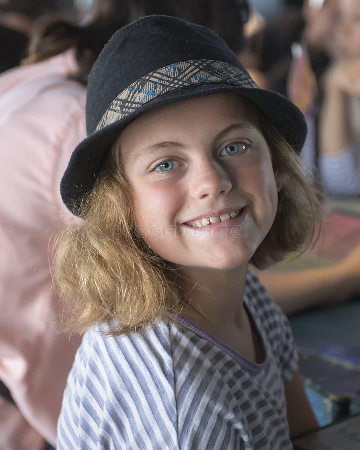 Primer de una sentada de diez años linda sonriente de la muchacha imagen de archivo libre de regalías