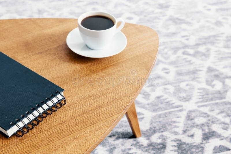 Primer de una tabla de madera con una libreta espiral y una taza de café con un fondo borroso de una manta modelada Foto verdader imagenes de archivo
