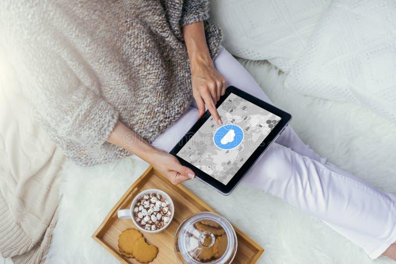 Primer de una tableta con el icono de la nube en la pantalla en las manos de la mujer joven que se sientan en casa Media sociales foto de archivo