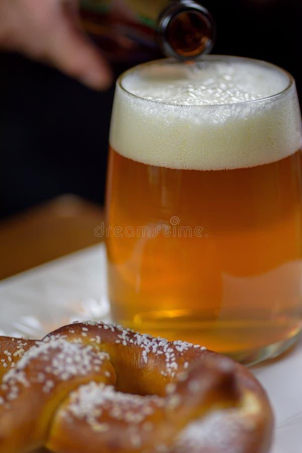 Primer de una taza de cristal grande de cerveza y de un pretzel suave imagenes de archivo