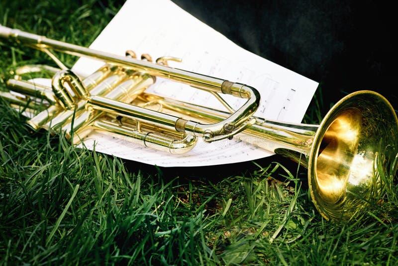 Primer de una trompeta y de una hoja de la música con las notas imagen de archivo
