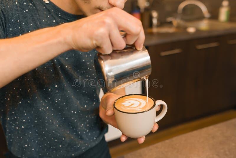 Primer de verter la leche cocida al vapor en la taza de café, fondo de la cafetería imagenes de archivo
