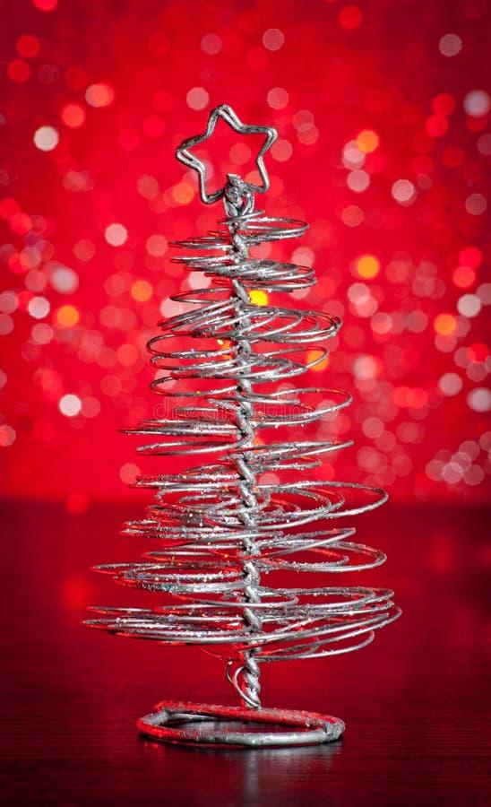 Primer del árbol de navidad moderno metálico en la tabla de madera foto de archivo
