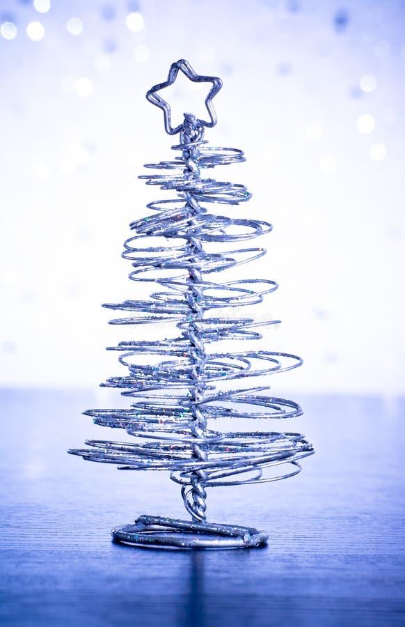 Primer del árbol de navidad moderno metálico en la tabla de madera foto de archivo libre de regalías