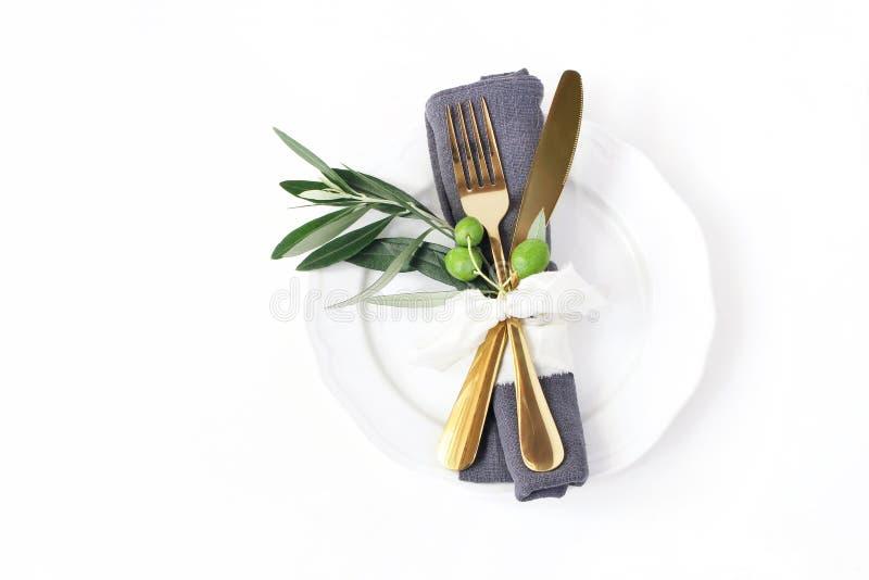 Primer del ajuste festivo del verano de la tabla con los cubiertos de oro, rama de olivo, servilleta de lino gris, placa de cena  foto de archivo libre de regalías