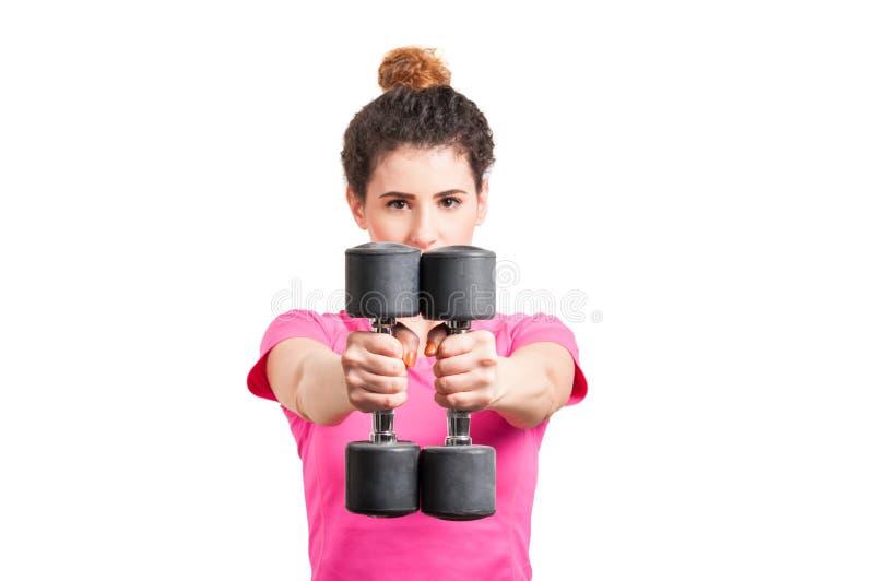 Primer del ajuste, mujer joven que amplía sus brazos con pesas de gimnasia fotografía de archivo libre de regalías