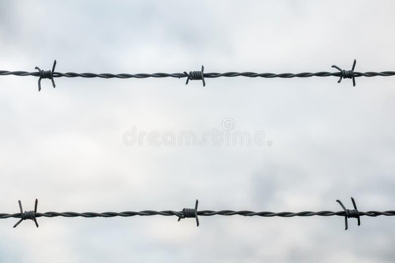 Primer del alambre de púas en dos líneas contra el cielo nublado imagen de archivo libre de regalías