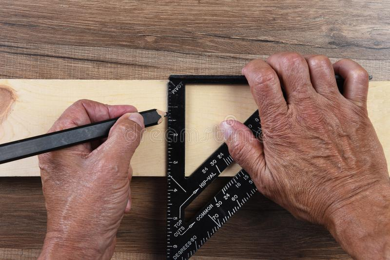 Primer del alto ángulo del manos de los carpinteros usando un cuadrado que enmarca para marcar una línea cortada en un tablero fotografía de archivo libre de regalías