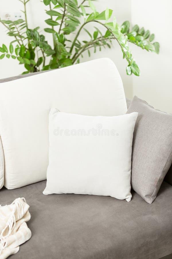 Primer del amortiguador decorativo blanco que miente en el sofá gris en la vida imagenes de archivo