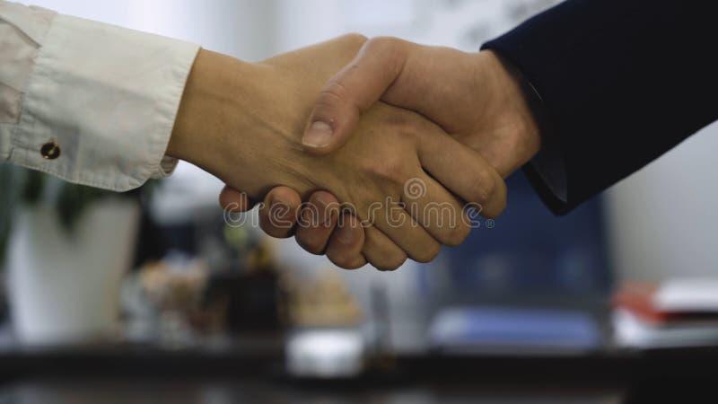 Primer del apretón de manos en el fondo de la oficina El buen negocio aseguró sociedad con el apretón de manos Dos compañeros de  fotos de archivo