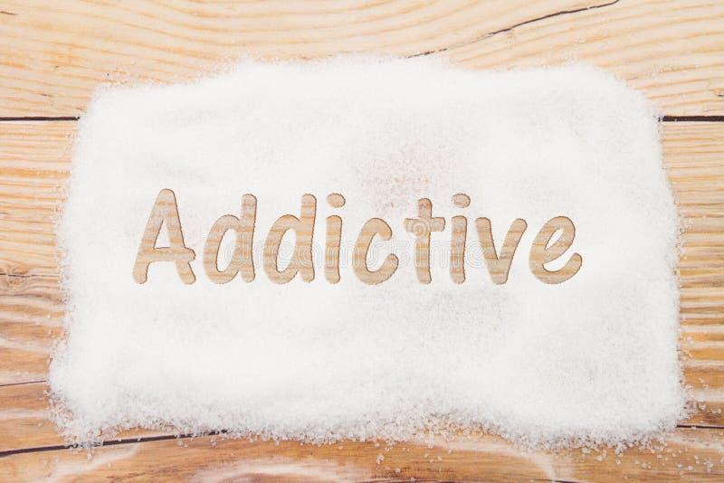 Primer del azúcar con el texto adictivo en backgrou de madera resistido imágenes de archivo libres de regalías