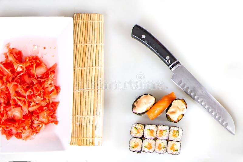 Primer del balanceo encima del sushi en la cocina con el cuchillo y los ingredientes imágenes de archivo libres de regalías