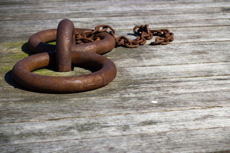 Primer del barco oxidado que amarra los anillos en muelle de la madera fotografía de archivo