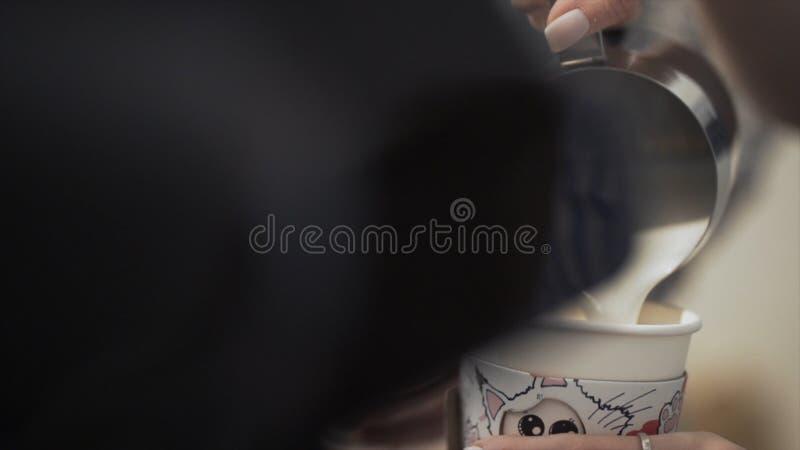 Primer del barista femenino que hace el café para llevar fresco acci?n Las manos de la mujer con la taza de leche para la prepara fotos de archivo libres de regalías