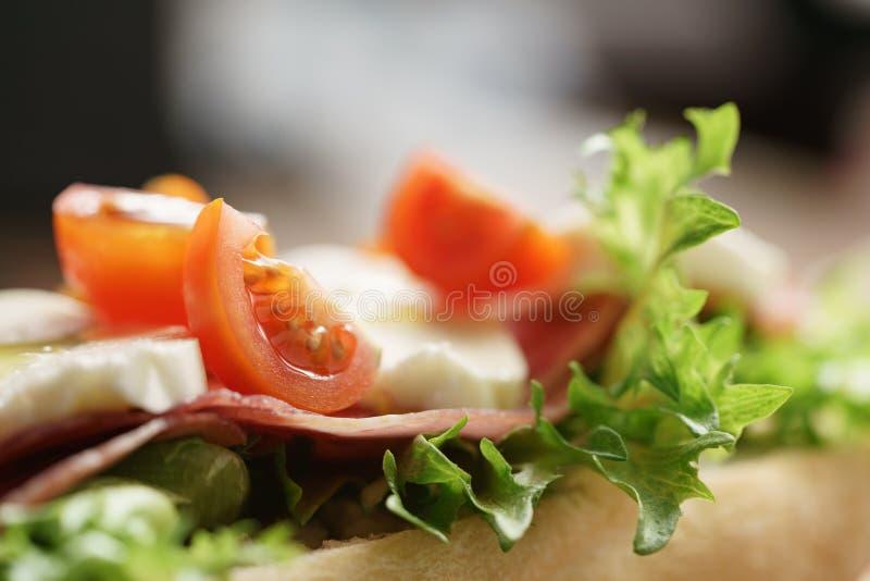 Primer del bocadillo abierto con el prosciutto, la mozzarella y los tomates en la tabla de cocina fotografía de archivo