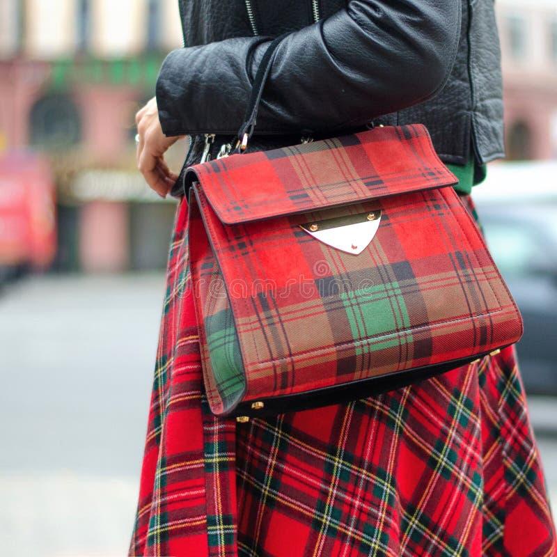 Primer del bolso en manos femeninas Imagen brillante, estilo Muchacha en una falda de tela escocesa roja fotos de archivo libres de regalías