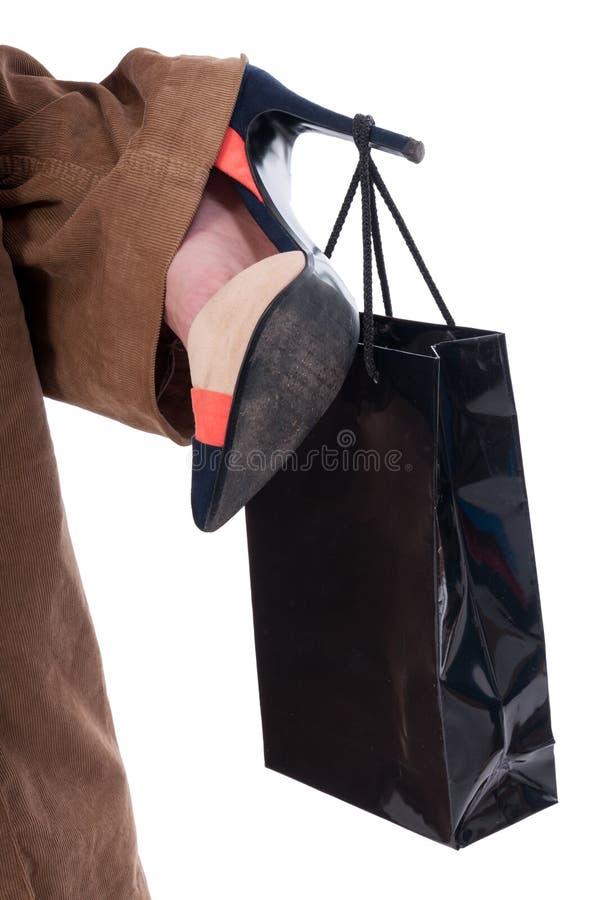 Primer del bolso que lleva de la mujer shopaholic en el talón imagen de archivo