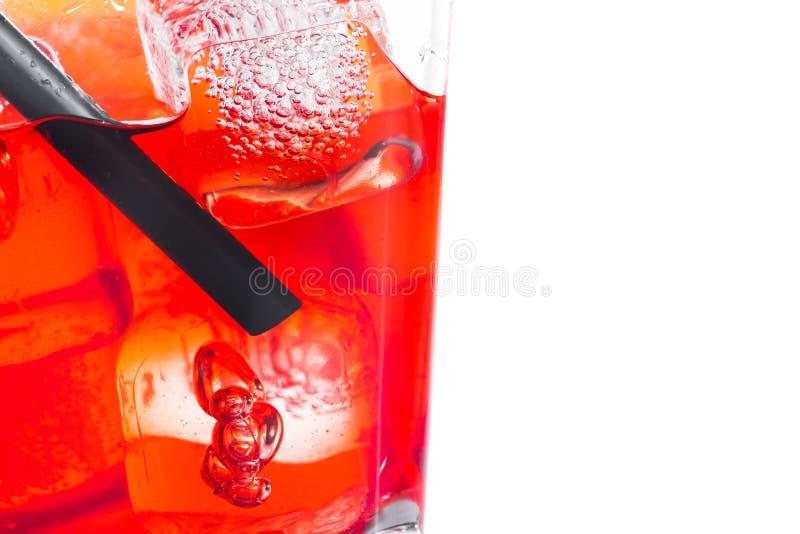 Primer del cóctel rojo con los cubos y la paja de hielo en el fondo blanco foto de archivo