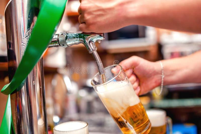 Primer del camarero que elabora una cerveza de barril en el pub Pourin del camarero fotografía de archivo libre de regalías