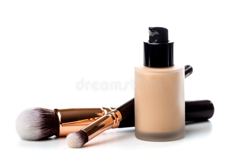 Primer del cepillo plano del maquillaje con el tubo líquido de la fundación aislado en blanco fotos de archivo libres de regalías
