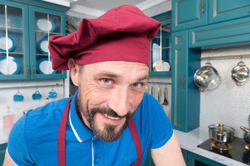 Primer del cocinero hermoso en sombrero con sonrisa a usted Hombre en delantal en la cocina Retrato del cocinero feliz fotografía de archivo