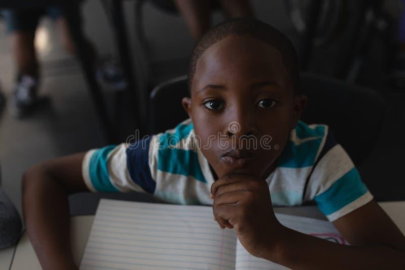 Primer del colegial negro con la mano en la barbilla que se sienta en el escritorio y que mira la cámara en sala de clase imagen de archivo libre de regalías