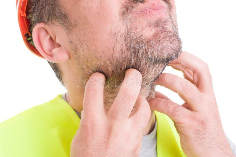 Primer del constructor de sexo masculino que rasguña su barba fotografía de archivo libre de regalías