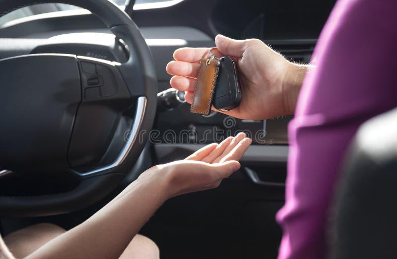 Primer del distribuidor autorizado que da llaves al comprador durante la prueba de conducción antes fotos de archivo