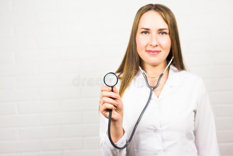 Primer del doctor de sexo femenino que usa el estetoscopio, foco en el estetoscopio foto de archivo