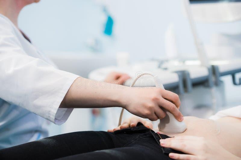 Primer del doctor Moving Ultrasound Probe en el estómago del ` s de la mujer embarazada en hospital fotografía de archivo libre de regalías