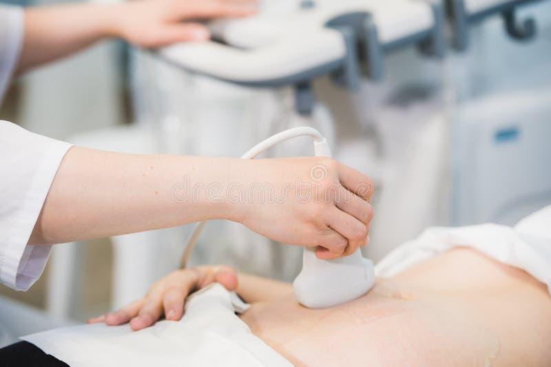 Primer del doctor Moving Ultrasound Probe en el estómago del ` s de la mujer embarazada en hospital fotos de archivo libres de regalías