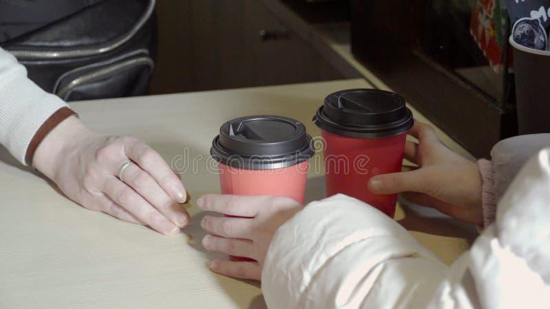 Primer del empleado del café que da bebidas El camarero sirve al cliente que da dos bebidas en tazas y que espera el siguiente imagen de archivo libre de regalías