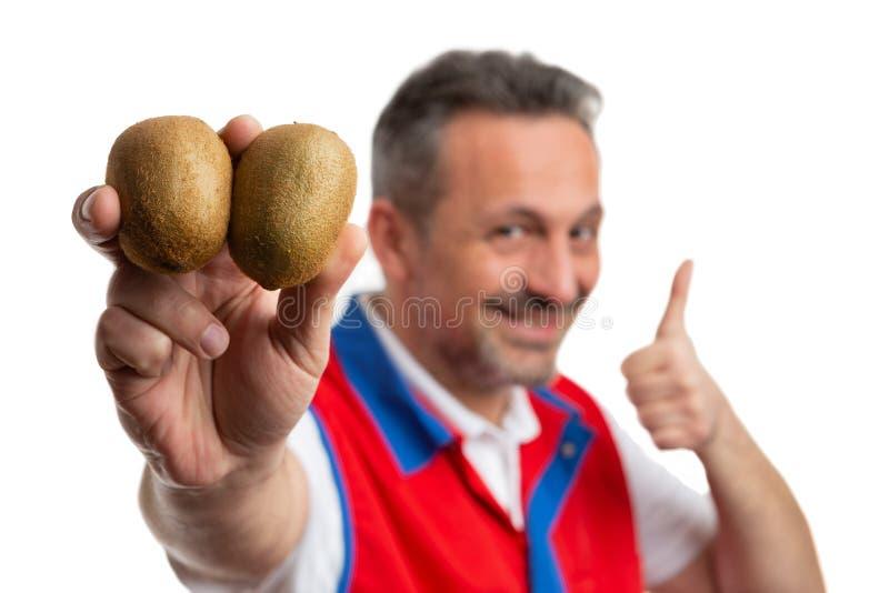 Primer del empleado del supermercado que presenta el kiwi y que hace el pulgar para arriba fotos de archivo