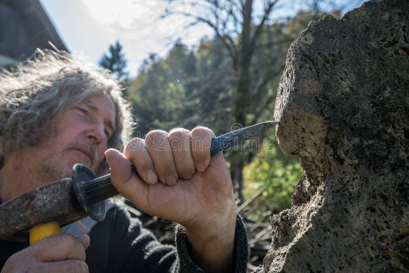 Primer del escultor mayor que usa el cincel y el mazo foto de archivo