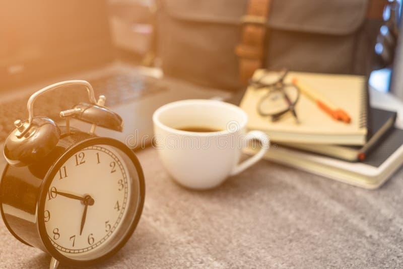Primer del estilo retro del vintage del reloj del negro de la alarma con el café blanco de la taza imagenes de archivo